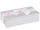 Ręczne pakowanie prezentu -Szarym papierem z ozdobną białą wstążką i różową  oraz różowymi kwiatkami.
